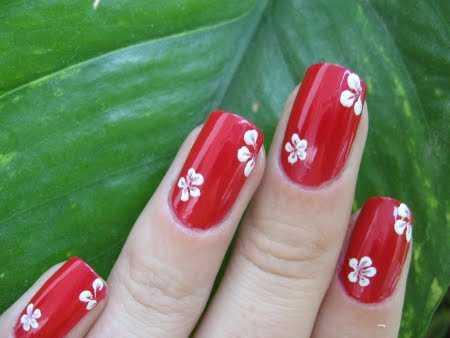 La clásica combinación de flores blancas sobre uñas rojas